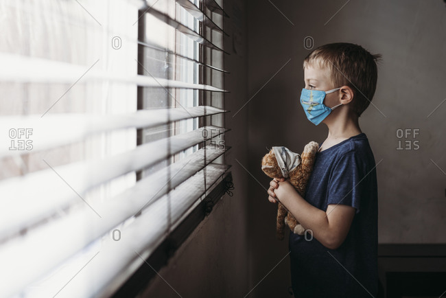 Side view of young school aged boy with mask on with stuffed animal