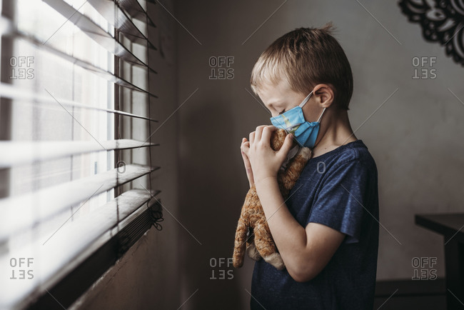 Side view of young school aged boy with mask on kissing stuffed animal