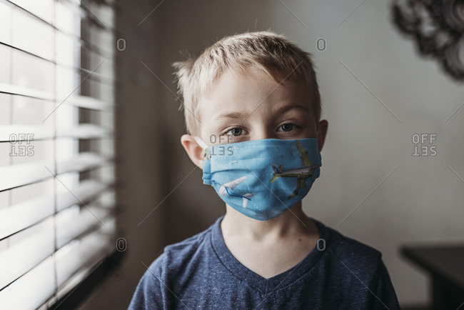 Portrait of young school aged boy with mask on with at home