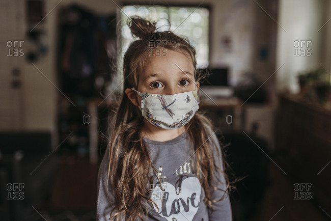 Close up portrait of young preschool aged brunette girl with mask on