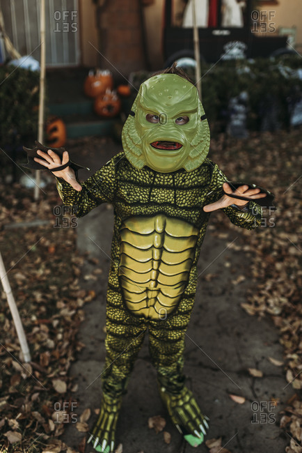 Young boy dressed as sea monster posing in costume at Halloween