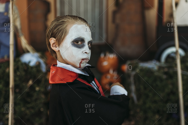 Young boy dressed as Dracula posing in costume at Halloween