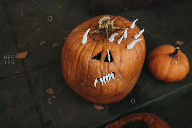 Close up of spooky carved pumpkin with teeth sitting on porch