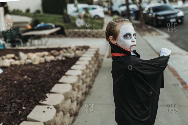 School aged boy dressed as Dracula Trick-or-Treating during Halloween