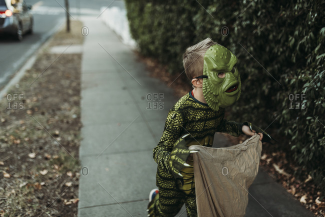 School aged boy dressed as monster Trick-or-Treating during Halloween