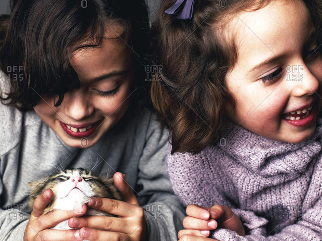 Two happy young girls with cat