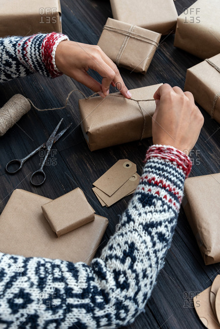 Female's hands in pullover enveloping Christmas gift box decorated with kraft paper