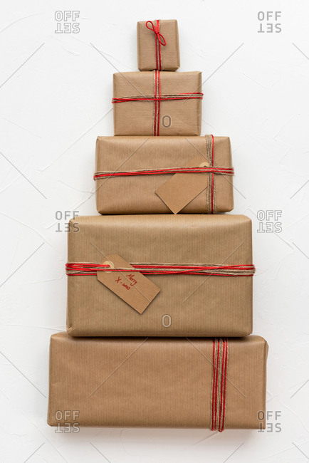 Christmas gift boxes wrapped in craft paper forming a Christmas tree figure on white background