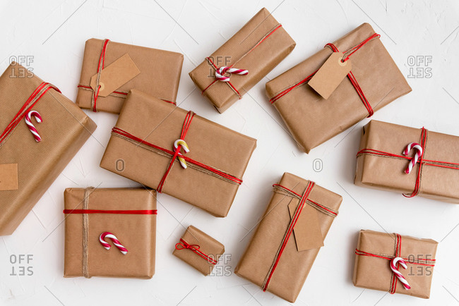 Christmas gift boxes wrapped in craft paper with red string and candy canes on a white background
