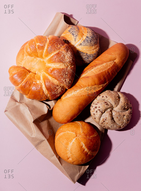 Overhead view of a variety of bread on a pink background