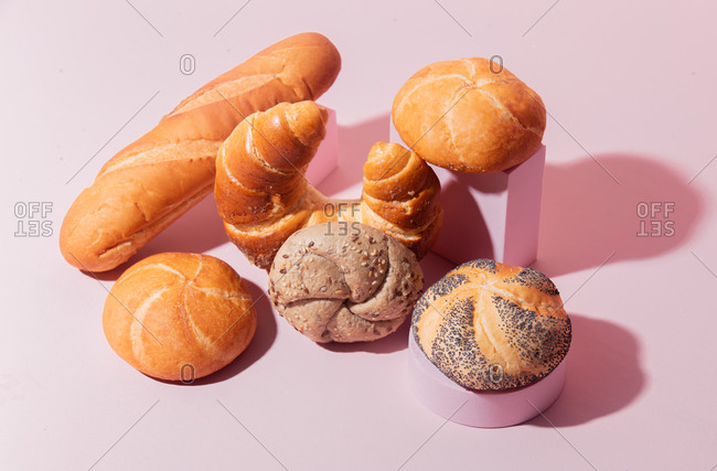 Top view of a variety of bread on a pink background