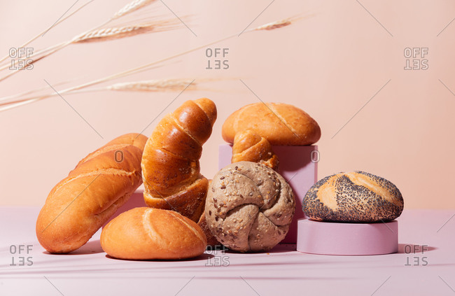 Variety of bread on a pink background with wheat spikelets