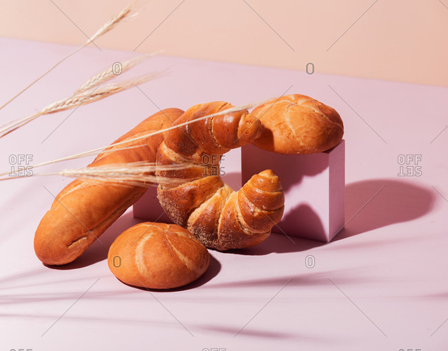 Bread with wheat spikelets on a pink background