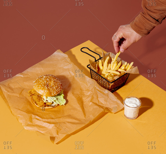 Male hand holding French fries near a chicken sandwich and sauce