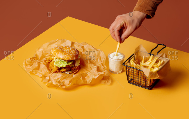 Man dipping a French fry in sauce beside a chicken sandwich