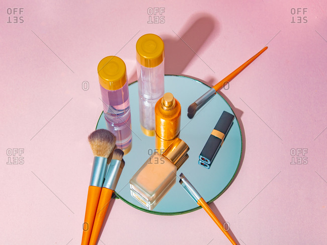 Cosmetics on a mirror on pink background viewed from above