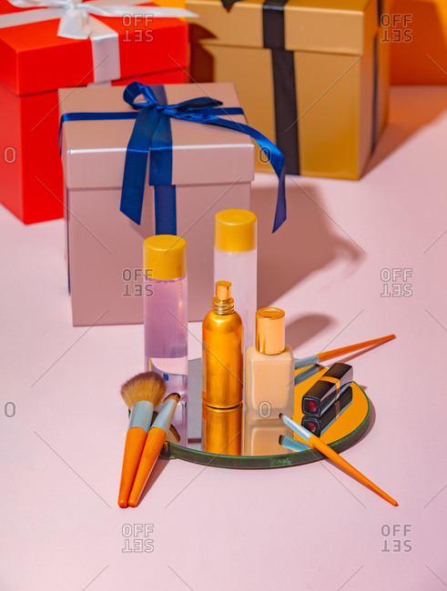 Cosmetics on a mirror beside gift boxes