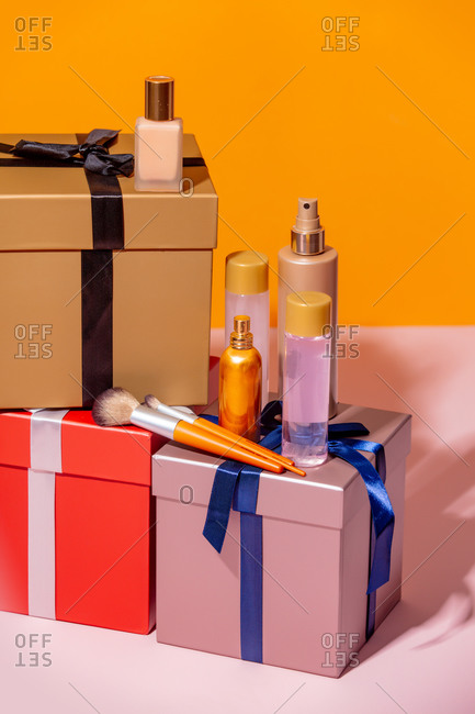 Cosmetic items and holiday gift boxes on a table
