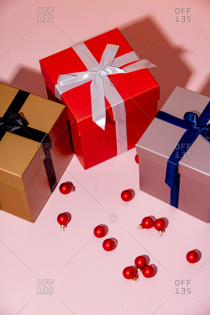 Overhead view of three holiday boxes and Christmas baubles on a pink table