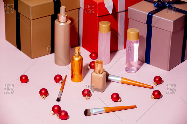 Holiday gifts and makeup on a table with red baubles
