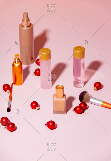 Makeup items and Christmas baubles on pink background