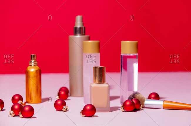 Makeup items and Christmas baubles on pink and red background