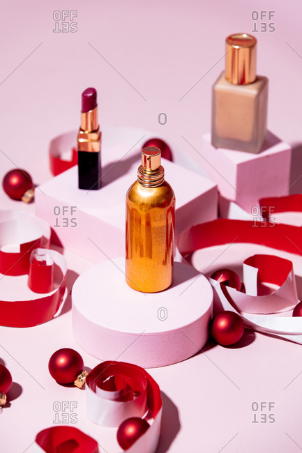 Close up of perfume, lipstick and cream foundation with Christmas decorations on pink background