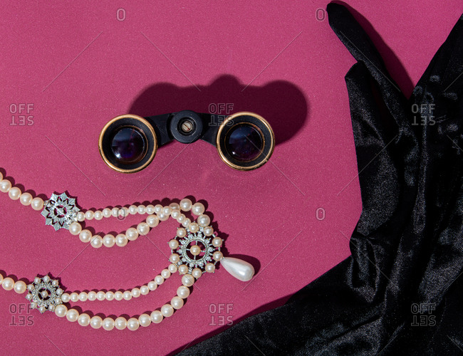 Pearl necklace, binoculars and gloves on purple background