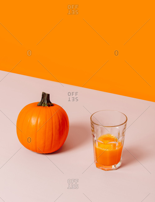 A pumpkin and juice on a table near orange background