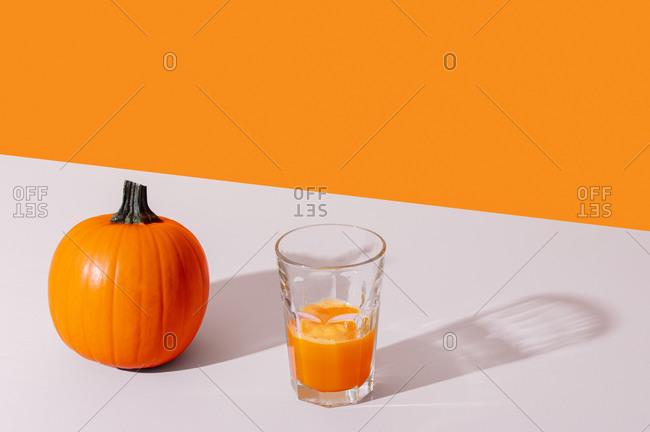 Glass of juice beside a pumpkin in front of an orange background