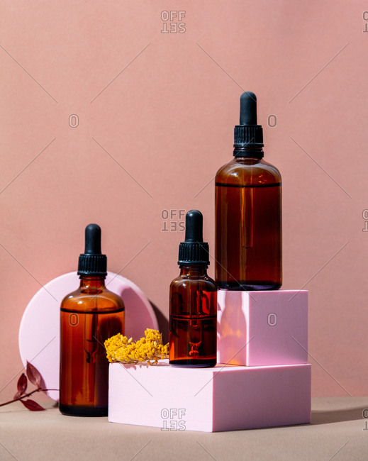 Oil bottles and geometric objects on pink background