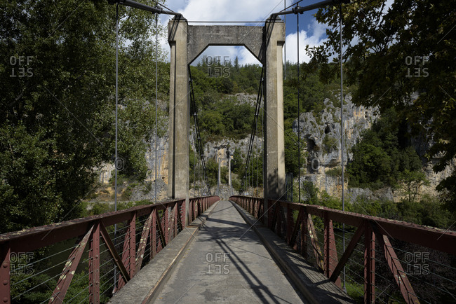 Old and narrow bridge over the river Lot to the town of Bouzies in the Lot department within the Occitanie region of southern France