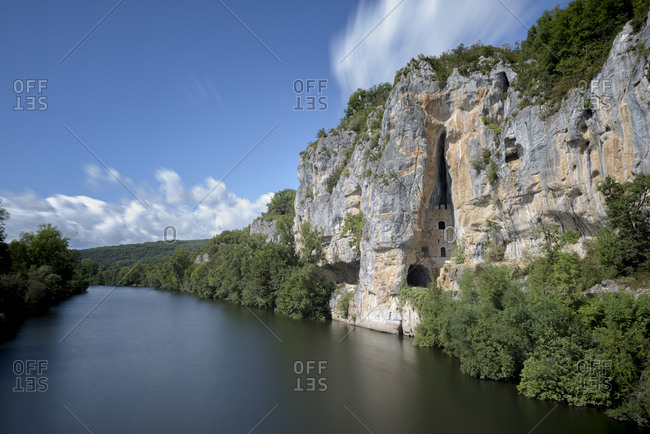 Cliffs and cliff dwellings on a sunny day along the Lot River and the D662 road in the Lot department within the Occitanie region of southern France