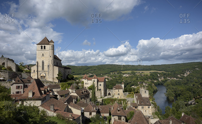 Church and homes in the medieval town of Saint-Cirq-Lapopie towering above the Lot River in the valley of the Lot in the Occitanie region in France
