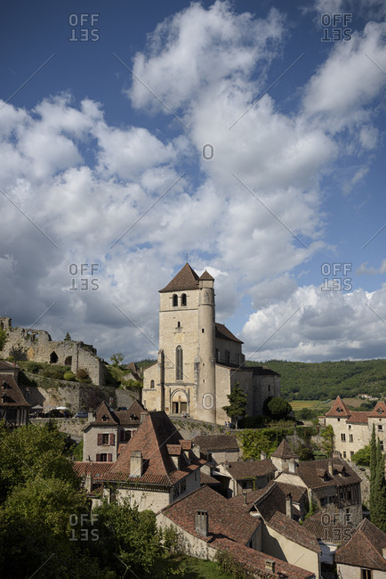 Large church surrounded by homes in the medieval town of Saint-Cirq-Lapopie in the valley of the Lot in the Occitanie region in France