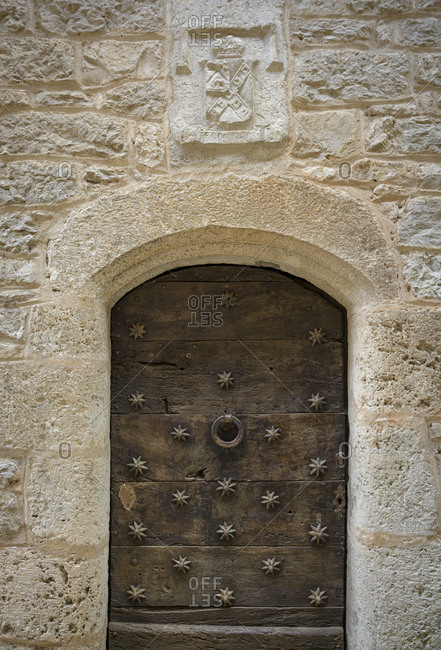 An old beautiful door and entrance with iron stars in the medieval town of Saint-Cirq-Lapopie in the Lot Valley in the Occitanie region in Franc