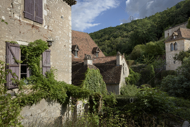 Old buildings surrounded by lush green trees in the medieval town of Saint-Cirq-Lapopie in the valley of the Lot in the Occitanie region in France