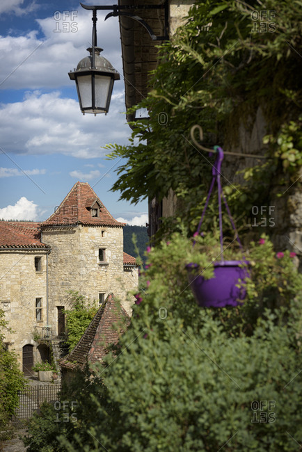 View of old buildings beyond trees in the medieval town of Saint-Cirq-Lapopie in the valley of the Lot in the Occitanie region in France