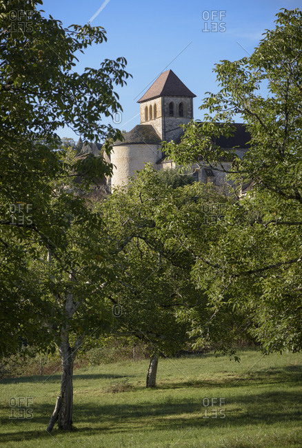 The small rural town of Montclera seen trough an orchard in the Lot department within the Occitanie region of France