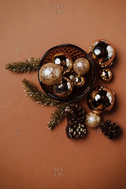 Shiny and glittering Christmas gold ornaments on brown background