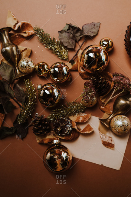 Scattered shiny and glittering Christmas ornaments in gold with ribbon and paper for text overlay