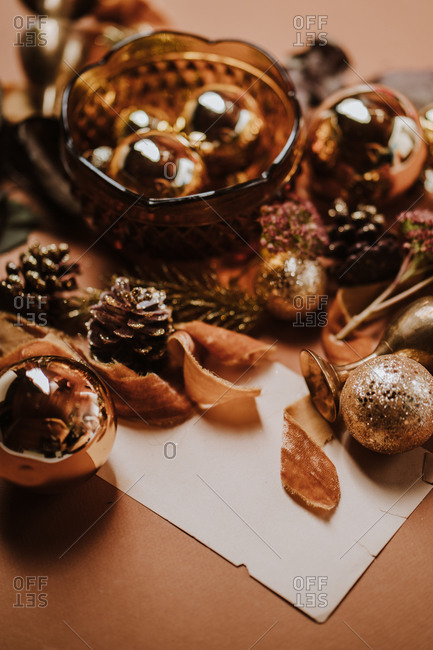 Golden table decor for Christmas including ribbon, balls, natural items, and paper for text overlay