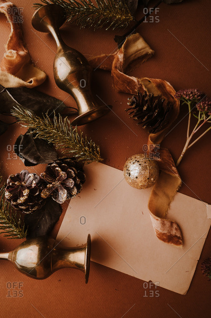 Warm holiday decor flat lay with ribbon, glittering pinecones and vintage paper for text overlay