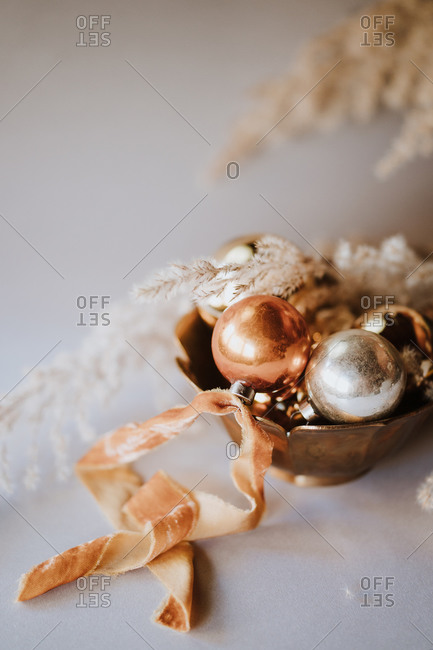 Christmas ornaments in gold and silver with organic materials in bowl on white surface