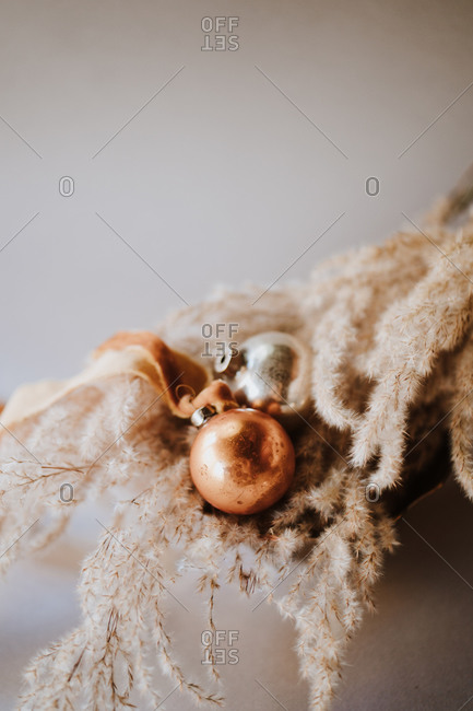 Top down view of Christmas ornaments in gold and silver with organic materials in bowl on white surface