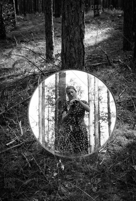Woman standing in the woods taking picture of herself in a round mirror resting on a tree in black and white