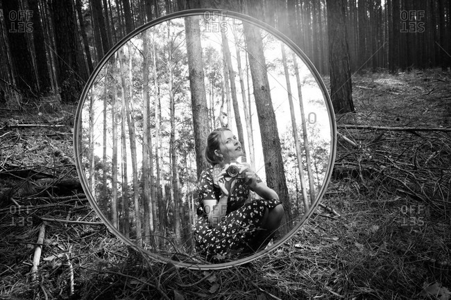 Woman taking picture of herself in a round mirror resting on a tree in black and white