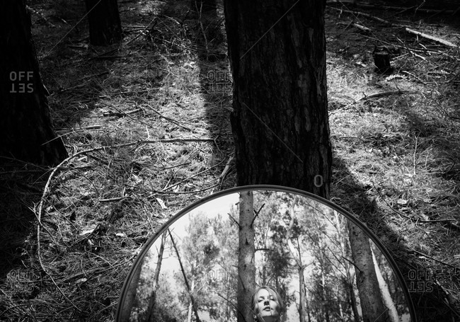Mirror resting on a tree with reflection of a woman's face in black and white