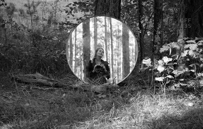 Female photographer taking a self-portrait in a round mirror resting on a tree in black and white