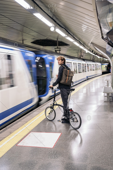 Young man in the metro holding his detachable bike.